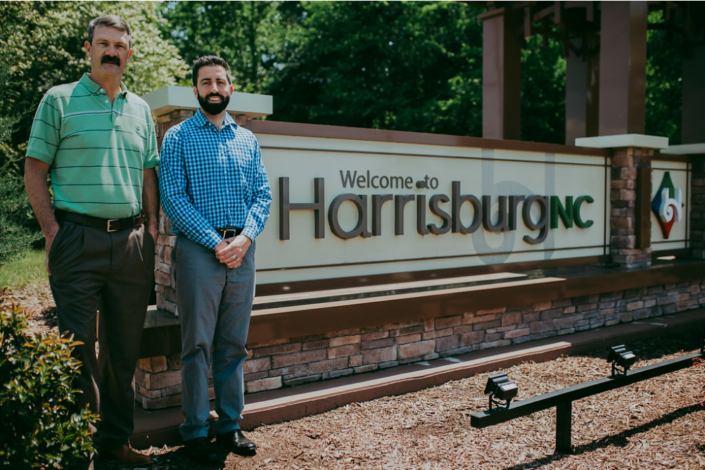 Drs Icard & Strein standing in front of Harrisburg NC sign